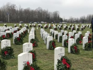 A cemetery with wreaths in front of every headstone