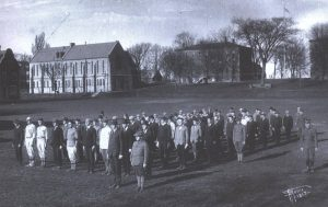 men standing in several rows with buildings in the background