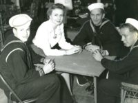 Three young sailors and a woman sit around a card table playing cards.
