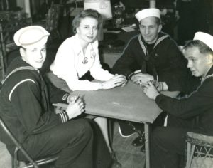 three soldiers and a woman sitting around a table playing cards