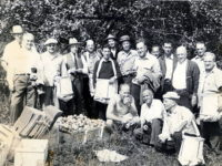 men-standing-in-an-orchard-with-boxes-of-apples