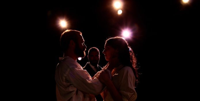 man and woman dancing under lights while another man watches