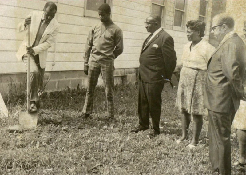 Three men and a woman watch a man dig with a shovel just outside a building.