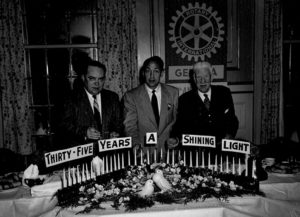 3-men-standing-with-candles-&-sign-35-years-a-shining-light