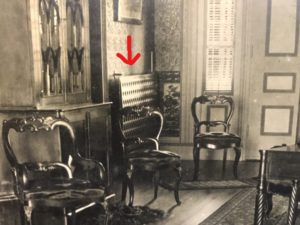 corner of a room containing three chairs, a radiator and a large piece of furniture