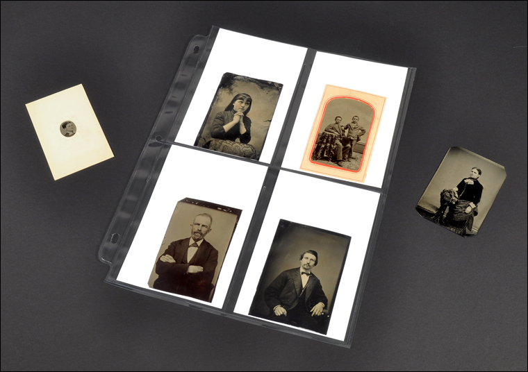 Six tintypes on a surface. Four are in an archival photo sleeve.