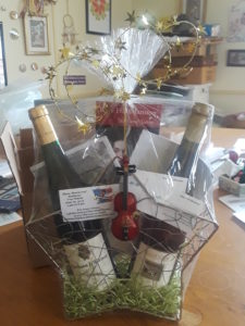 gift basket filled with wine, tickets and an ornament