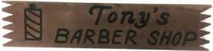 """Handmade wooden sign with a barber pole and """"Tony's Barber Shop"""" painted on it."""