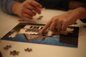 Hands putting together a jigsaw puzzle of a house