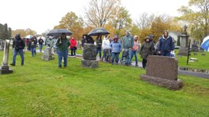 People walking in a cemetery in the rain