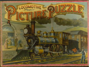 """Color illustration of a train arriving at a station labeled """"Locomotive Picture Puzzle."""""""
