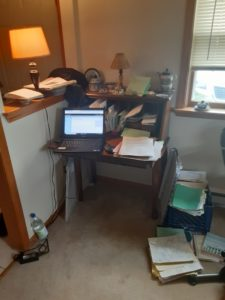 small desk with lap top and folders surround by a water bottle, folders, and notebooks