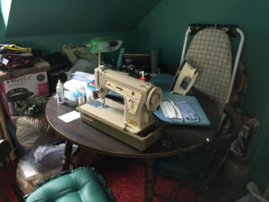 A table with sewing machine, iron, sewing materials and masks on it.