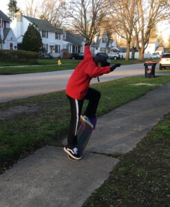 Boy doing an ollie on a skatboard on the sidewalk of a suburban street.