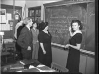 woman pointing at writing on a chalkboard with writing on it with three adults looking on