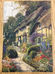 English cottage surrounded by flowers and shrubs with a woman at the front door
