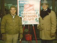 Two Older Men In Coats Ringing Bells For Salvation Army