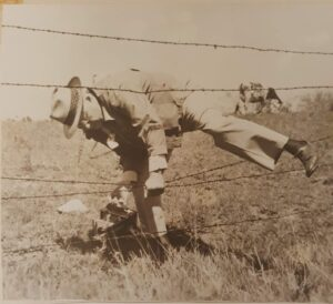a man climbing over a barbed wire fence