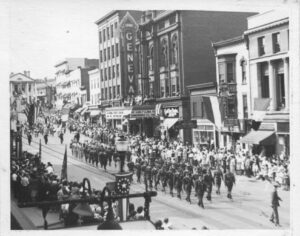 Soldiers marching down a dowtown street.