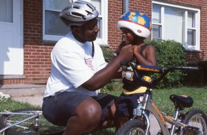 African American Man & Boy With Bicycle Helmets