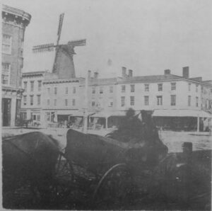 A wagon with a downtown intersection and grist mill in the foreground