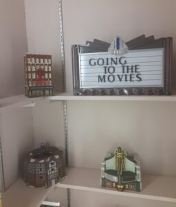 """Three theater models and a sign """"Going to the Movies"""" sitting on shelves."""