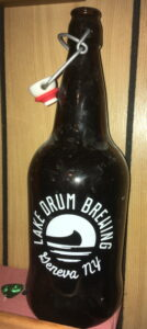 """Brown glass bottle with """"Lake Drum Brewing Geneva, NY"""" and an image of a canoe in the water printed on it."""