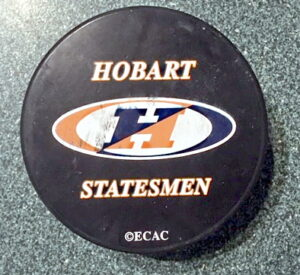 """Black hockey puck with """"Hobart,"""" """"Statesmen"""" and a large """"H"""" printed on it"""