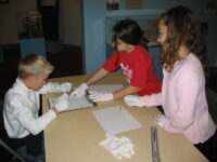 A boy and two girls around a table wearing white gloves and writing.