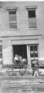 A horse drawn wagon in front of a brick storefront.  Three people are sitting in the wagon and one person is sitting on the ground along side the horse.