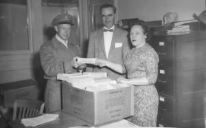 two men and a woman standing behind a box on a desk in an office