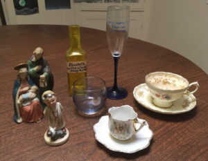 Two tea cups, from my grandmother, a glass, a Napco figurine, a statue of the Holy Family, a bottle and a champagne flute