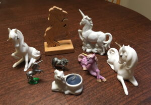 A collection of unicorn figurines that are made from a variety of materials