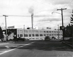 View of a factory with 1950s cars and a truck driving by.