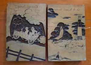 two printing blocks.  One contains an automobile with two people.   The other is a sailboat on the water with a lighthouse