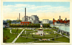 Postcard image of people in a lakeside part with factories in the background