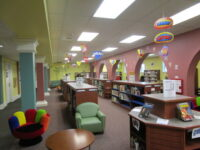 Brightly colored room with books shelves, tables and chairs.