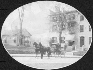 horse and buggy in front of a single story building and a multi-story building