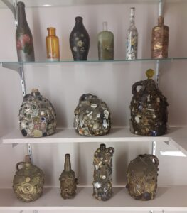 One shelf has painted bottled and two shelves have memory jugs